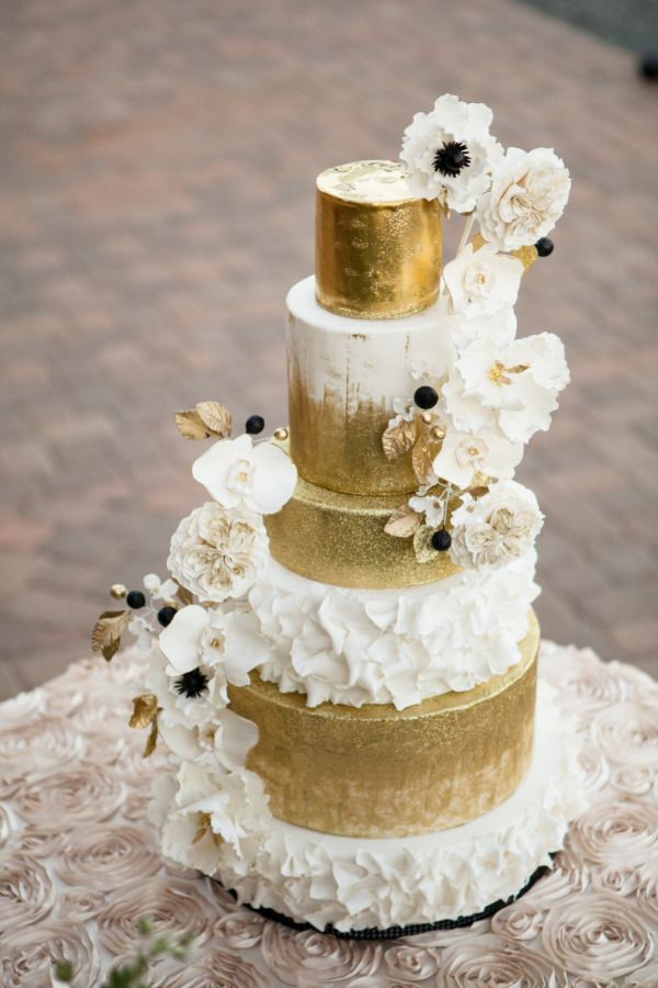 gold and white wedding cake with flowers