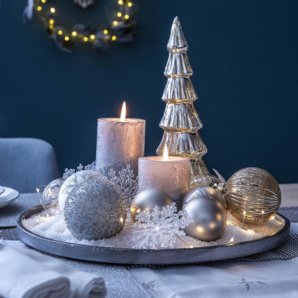 Ein silbernes Dekotablett mit Kerzen, Tanne und Kugeln zaubert ...