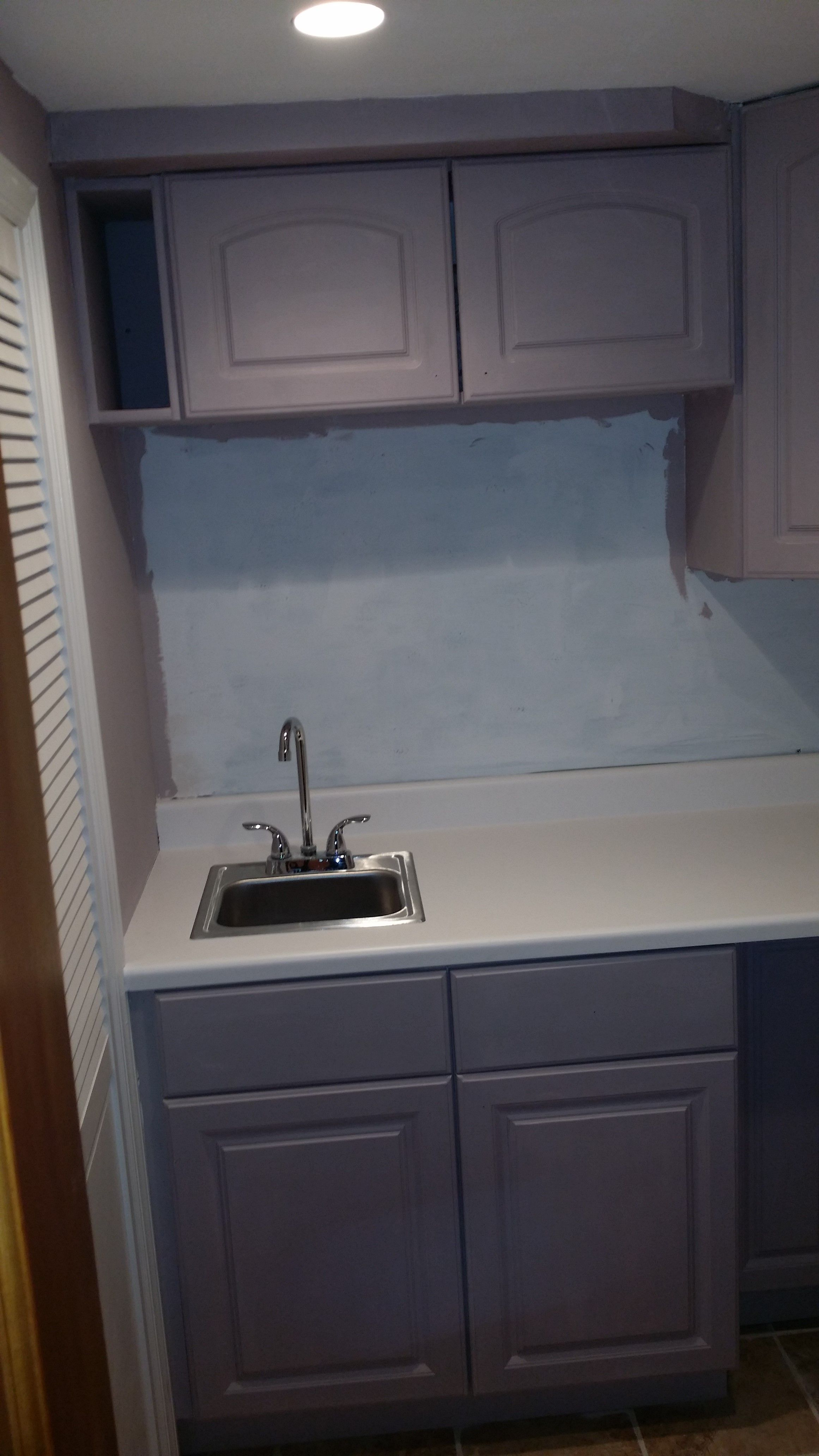 Laundry Room Before white melamine cabinets from Home Depot paint