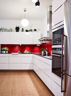 A red touch to a stylish white kitchen