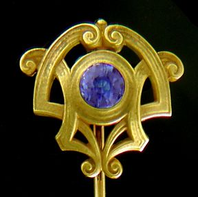Intertwining golden scrolls centered with a rich blue sapphire.  The flowing, interlacing curves reflect the sinuous style of the Art Nouveau, as well as the intricate Celtic Revival designs of the early 1900s.   Crafted in 14kt gold,  circa 1900.