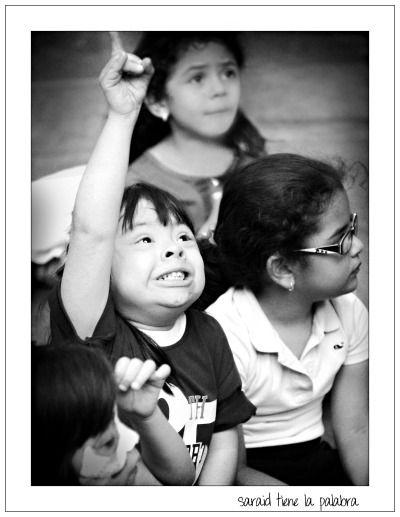 Niña con síndrome de Down alzando la mano