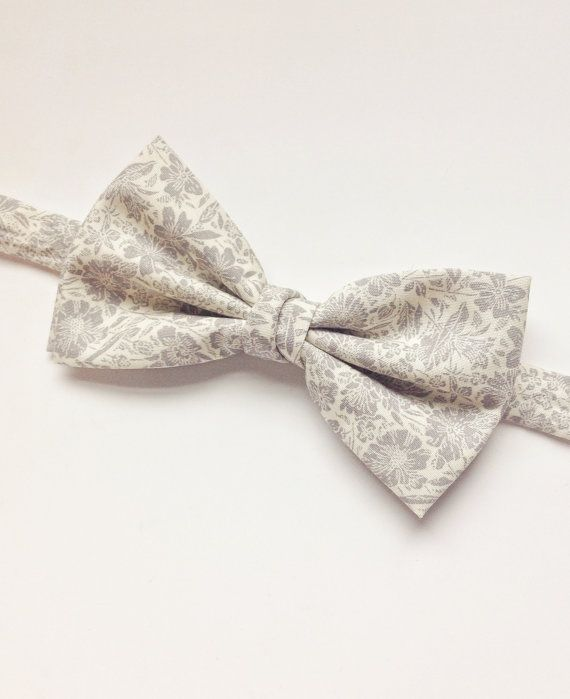 DESCRIPTION: This beautiful soft grey floral cotton makes for the ideal wedding bow tie. It has a double bow and twisted central loop for extra fullness. FABRIC: 100% Cotton  --------------------------------------------------------------------------------------------  DETAILS: • This bow tie is pre-tied • Attached to an adjustable strap fitting approx 15inch - 19inch neck size • Neatly packaged in a smart box with ribbon and tag attached • Lovingly handmade in the UK • Postage - UK delivery…