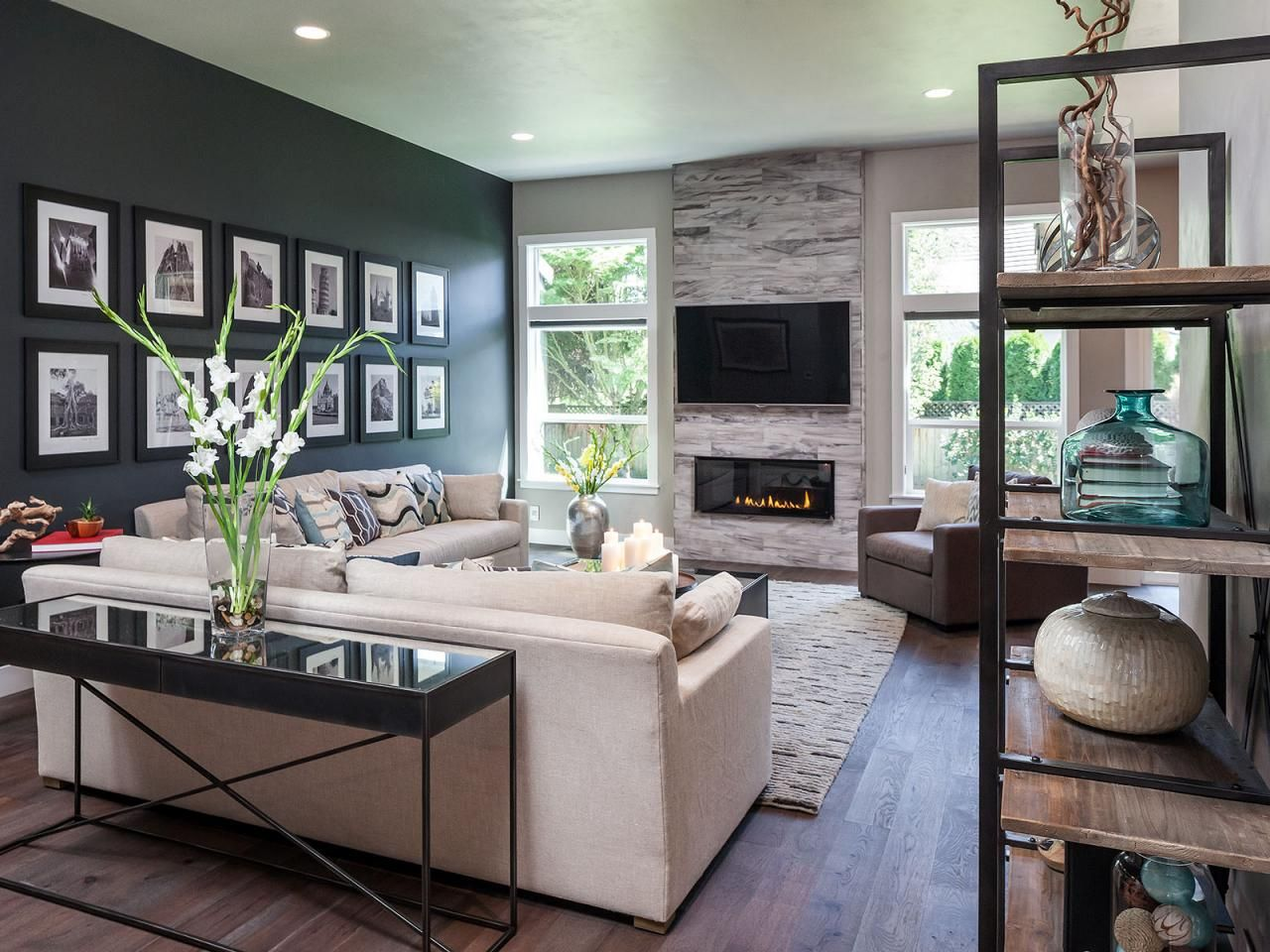 A Sophisticated, Modern Living Room Features A Dark Accent Wall And  Fireplace That Adds A