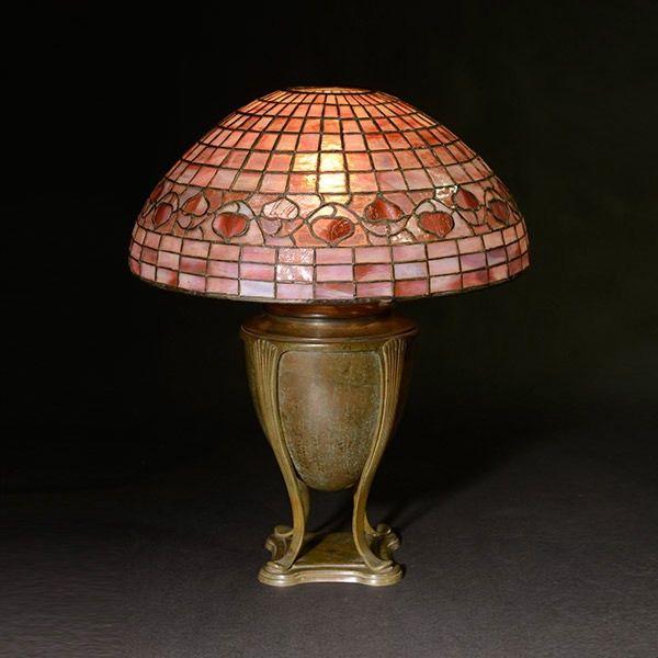 """Lampara de mesa """"Acorn"""" """"Bellota"""". La pantalla, de pequeñas teselas trapezoidales en tonos rosados  rojizos, tiene una cenefa de bellotas. La base, sostenida por cuatro patitas sobre un pie cuadrado,  es la urna original que contenia el recipiente de aceite con que funcionaba la lampara. Mide 50,8 cm de alto y 40,64 de diametro de pantalla. Se"""