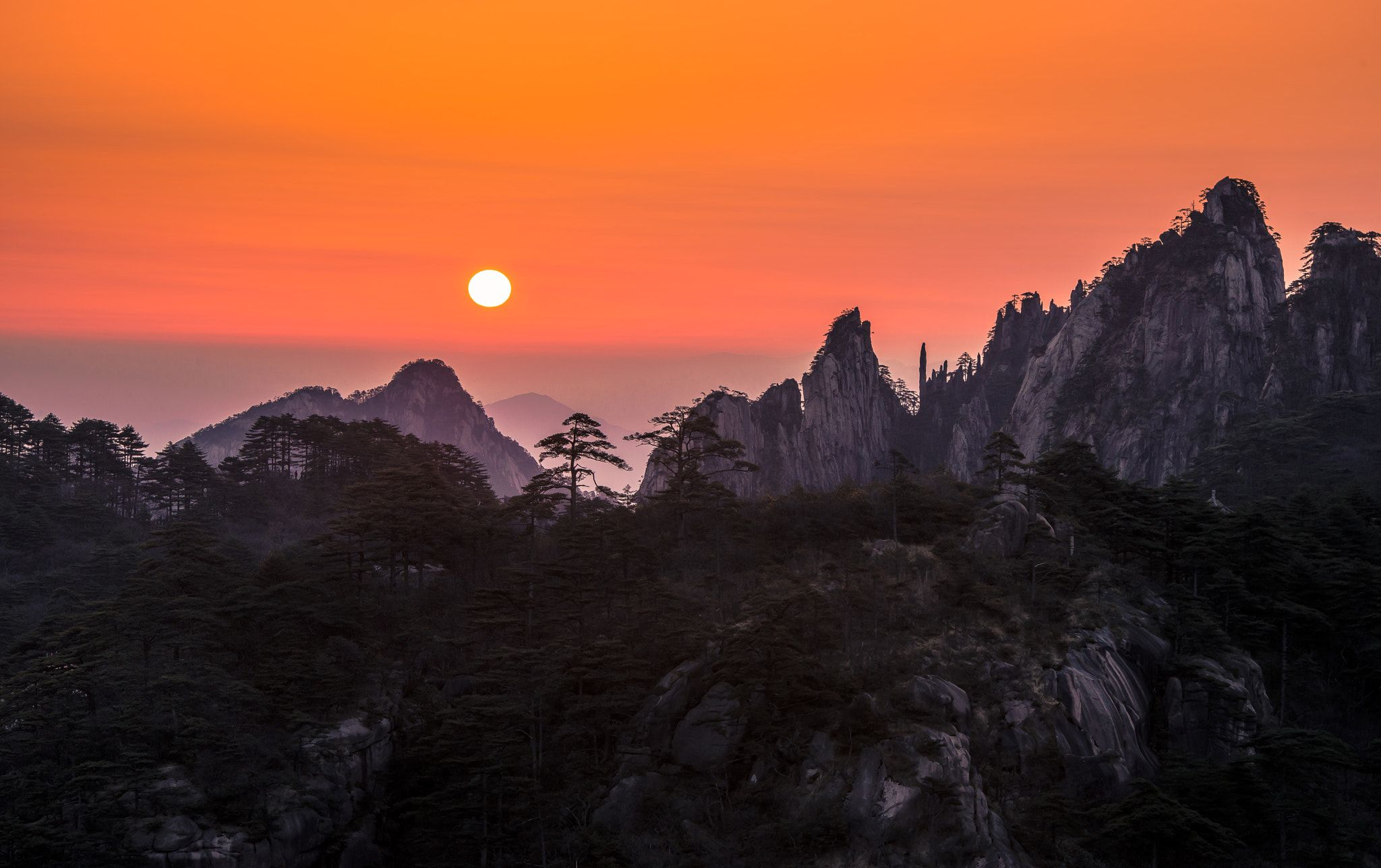 """Sunrise at Huangshan - Huangshan is known for its sunrises, pine trees, """"strangely jutting granite peaks"""", and views of clouds touching the mountainsides. The Huangshan mountain range has many peaks, some more than 1,000 meters (3,250 feet) high."""