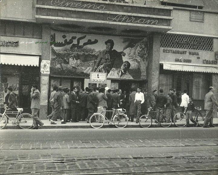 سينما الاهرام في شارع بور سعيد وخطوط الترام المؤود شاهد وغالبة الرواد مرتدية للاطقم خمسينيات القرن العشرين