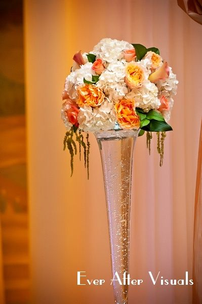 Tall fluted glass vases with florals in white, orange and peach.