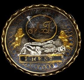 """1700 mourning slide. The wearer would have thread a ribbon through the loops on the back and worn this as a bracelet or collar necklace. The materials here are hair, gold foil and enamel, all fitted under rock crystal. The skeleton, presumably of the deceased, is lounging on his/her coffin, which is engraved with the words """"I rest."""""""