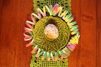 In Finland we deep-fry sweets for May Day - like doughnuts. This is a photo of a doughnut in an amazing cabbage leaf plate, surrounded with rainbow streamer on a green crocheted lace runner... it cannot get more Mayday-y for me! :-D (Well... a Finnish blog. What would you expect? :-D)