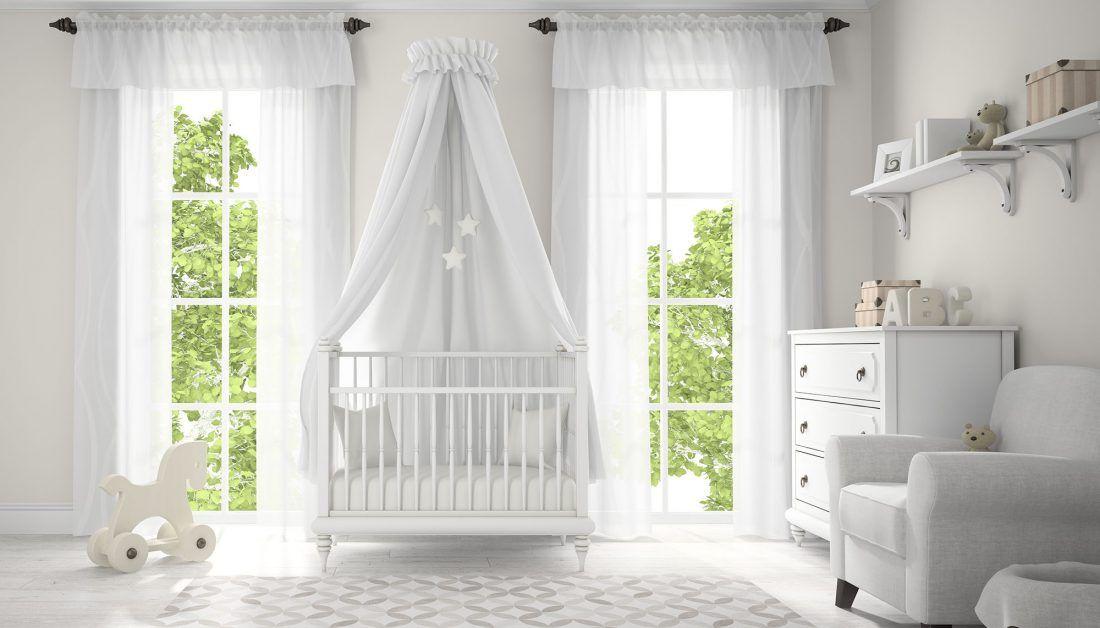 modernes babyzimmer in weiß mit himmelbett sessel und