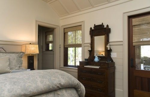 This bedroom would have felt old-fashioned were it not for the unusual ceiling and wainscot treatments. Painting the wainscoting a few shades darker than the walls helps to ground the space.