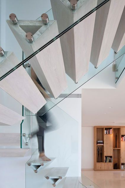 Wooden triangular stair treads and glass railing are anchored by stainless steel stand outs in this modern Tel Aviv home. (staircase by Gerstner)