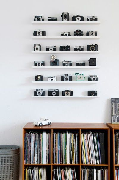 Camera collection can be displayed in various ways and one of the simplest and safest ways to display them is to arrange them neatly on a shelf in your living room. You can place them above a bookshelf or by the side of television to make it look neat. Also, when these cameras are placed in a shelf, it will be safe and you needn't worry about falling down or damage to it.