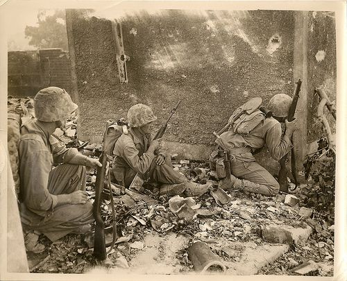 6th Division Marines Pinned Down in Okinawa Temporarily, during their fight among the wrecked homes & rubble of Naha, capital city of Okinawa island, Sixth Division Marines are pinned down by the fire of the Japs. They take cover behind a wall and one peers cautiously around the corner to see what is ahead of them. The first two on the left pack M-1 carbines, the third looking around the corner a Garand rifle.1945