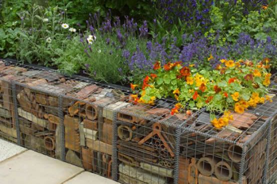 Cube-shaped gabion box filled with deserted bricks and tiles forms a unique view in the garden