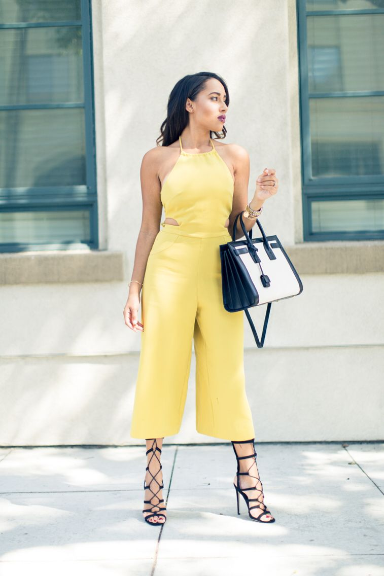 Black dress yellow heels - A Pastel Yellow Culotte Jumpsuit Paired With Strappy Black Heels And A Tote Bag