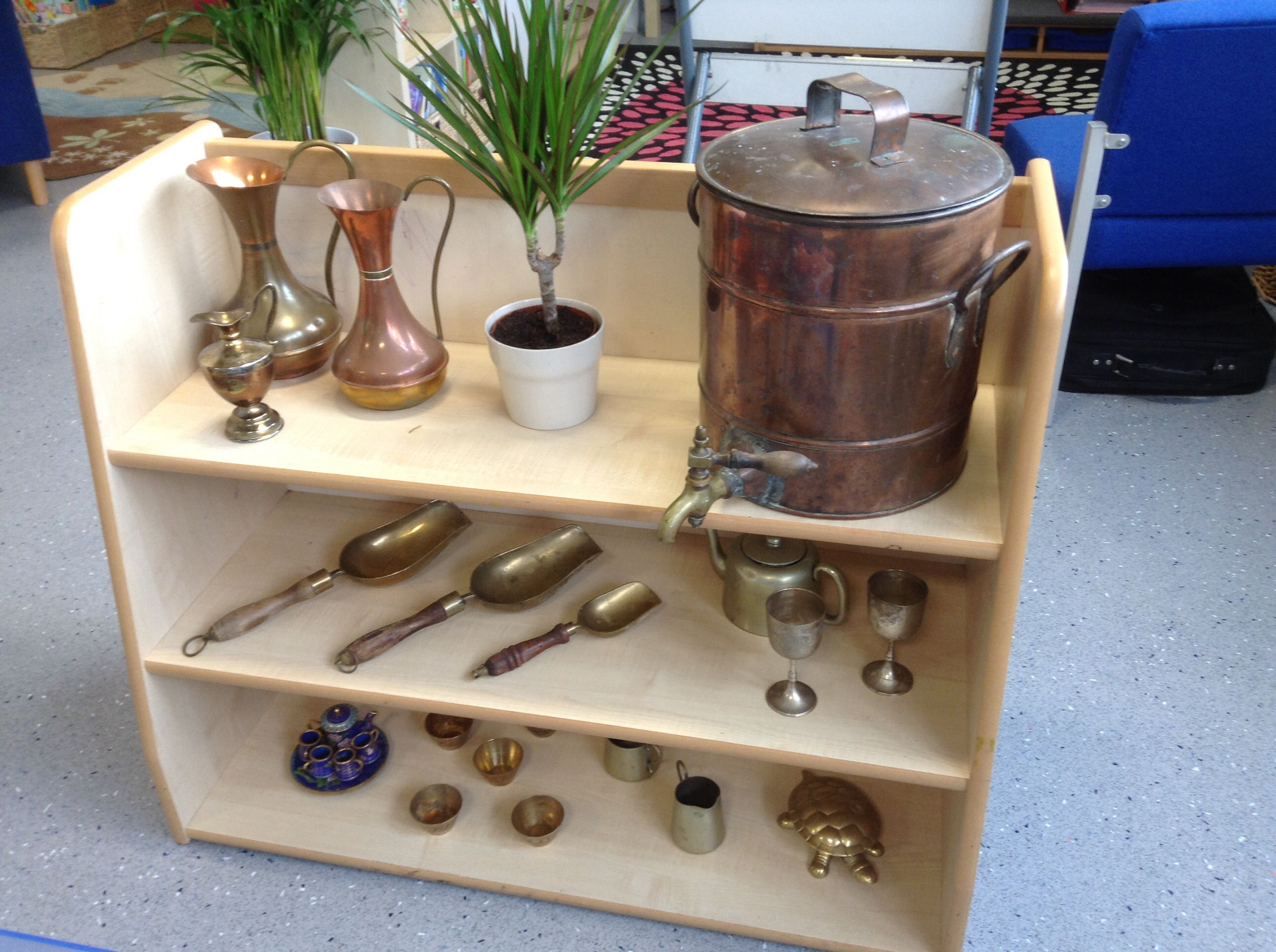 Water play shelf.  We have changed all of our water resources to brass to create a greater sensory experience of  the children. The weight, texture, shiny reflective surfaces etc all create more talking and exploring points than the plastic resources, and are a lot more exciting for them to use!
