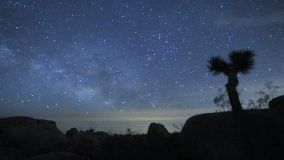 Majestic long-exposure time lapse shot of the Milky Way and Stars Galaxy. Passing over Joshua Tree Desert. Fades up to an overexposed white as the sun rises.