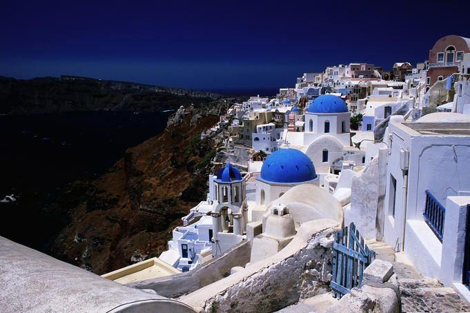 Greek Islands. White-washed houses and blue domes on cliff top.