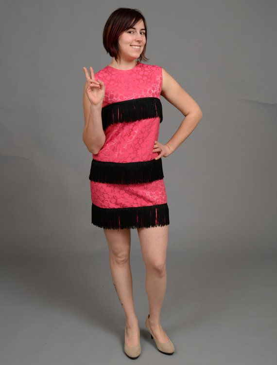 ($38.00) This dress is 100% groovy, baby! Straight out of the 1960s, this super mod mini features a pink satiny fabric, zipper up the back, and 3 tiers of black fringe.  This dress fits like a women's small/ size 4. Measurements: Bust- 34in Waist- 34in Hip- 34in  The model shown is a 6/8. The dress just barely zipped up on the model.