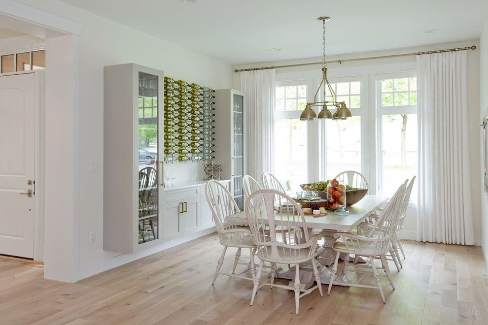 This light wood floored dining room showcases a ...