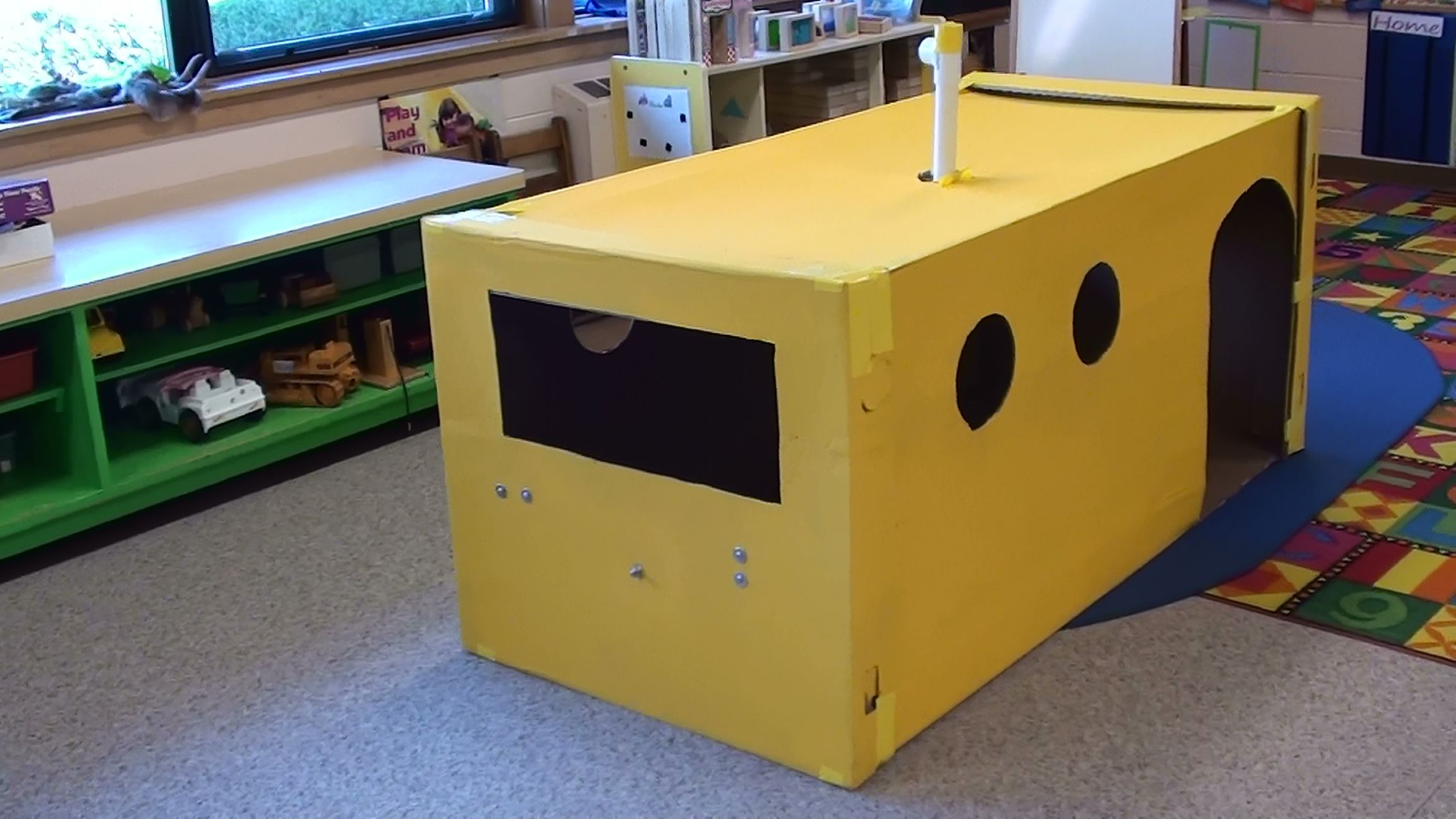 Create a submarine out of a freezer box.  Cut out portholes, front window, and door.  Screw on a steering wheel--I used a bucket lid (use large washers on both sides of cardboard to allow it to spin easily).  Print out a variety of gauges and glue them on the inside walls. Our 4K class loved it.