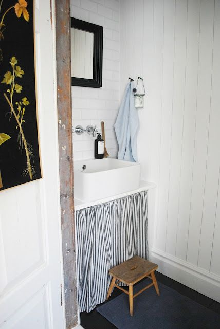 bathroom with ticking stripe skirt.