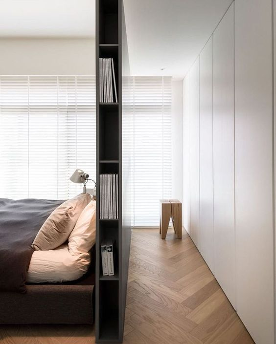 Photo of Armadio proprio dietro un letto alto con spazio laterale per libri e …