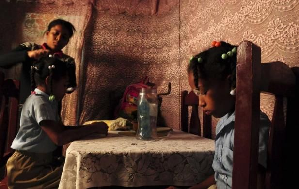 International Women's Day: Single mother Evelyn de los Santos combs the hair of her daughters to prepare them for school in Capotillo, at a slum of some 100,000 inhabitants along Ozama River in Santo Domingo, March 7, 2012. REUTERS-Ricardo Rojas
