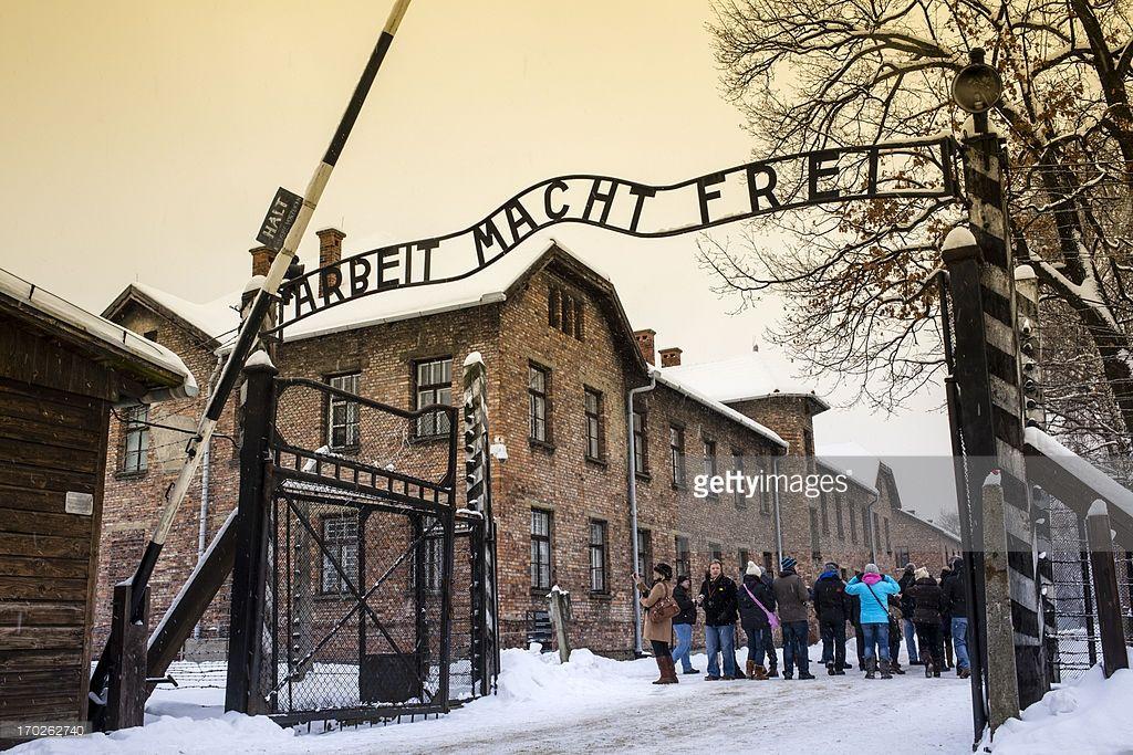 Tourists under Arbeit macht frei sign at Auschwitz Concentration Camp, a UNESCO World Heritage Site, Oswiecim near Krakow, Poland, Europe.