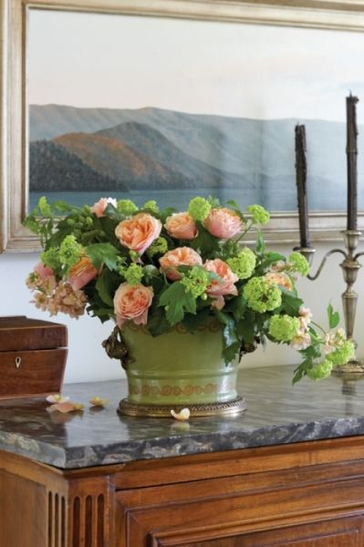 A cachepot spilling over with pink and green blooms echoes the palette of the lakescape behind it.