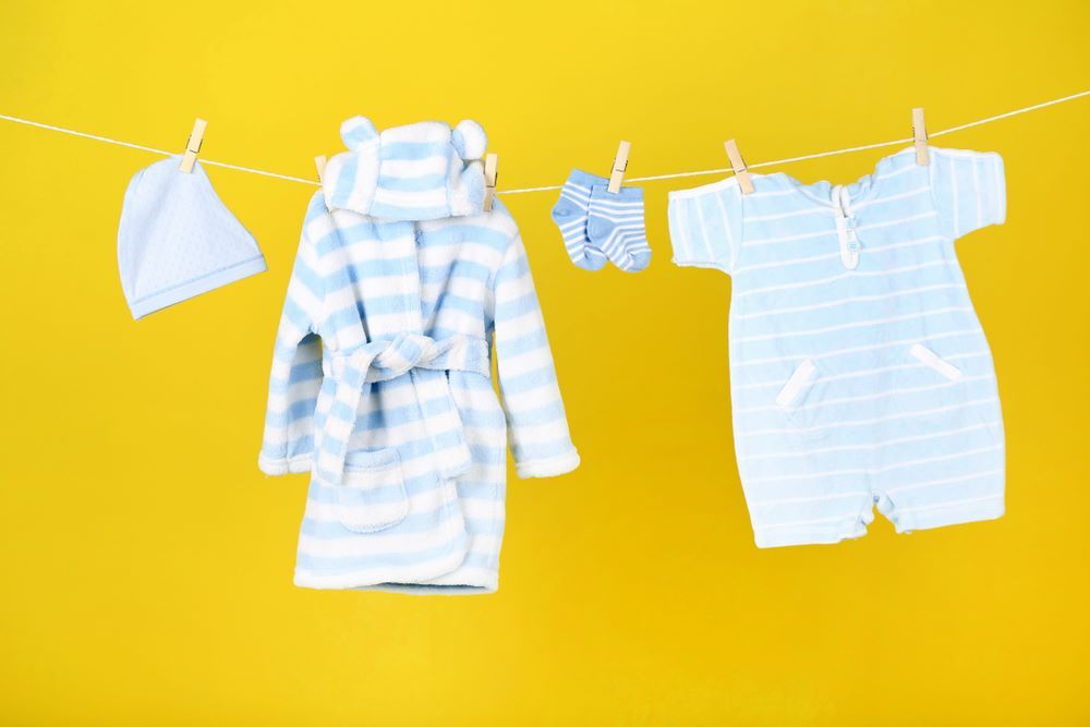 Baby Clothes Hanging On Yellow Background Baby Clothes Hanging On Yellow