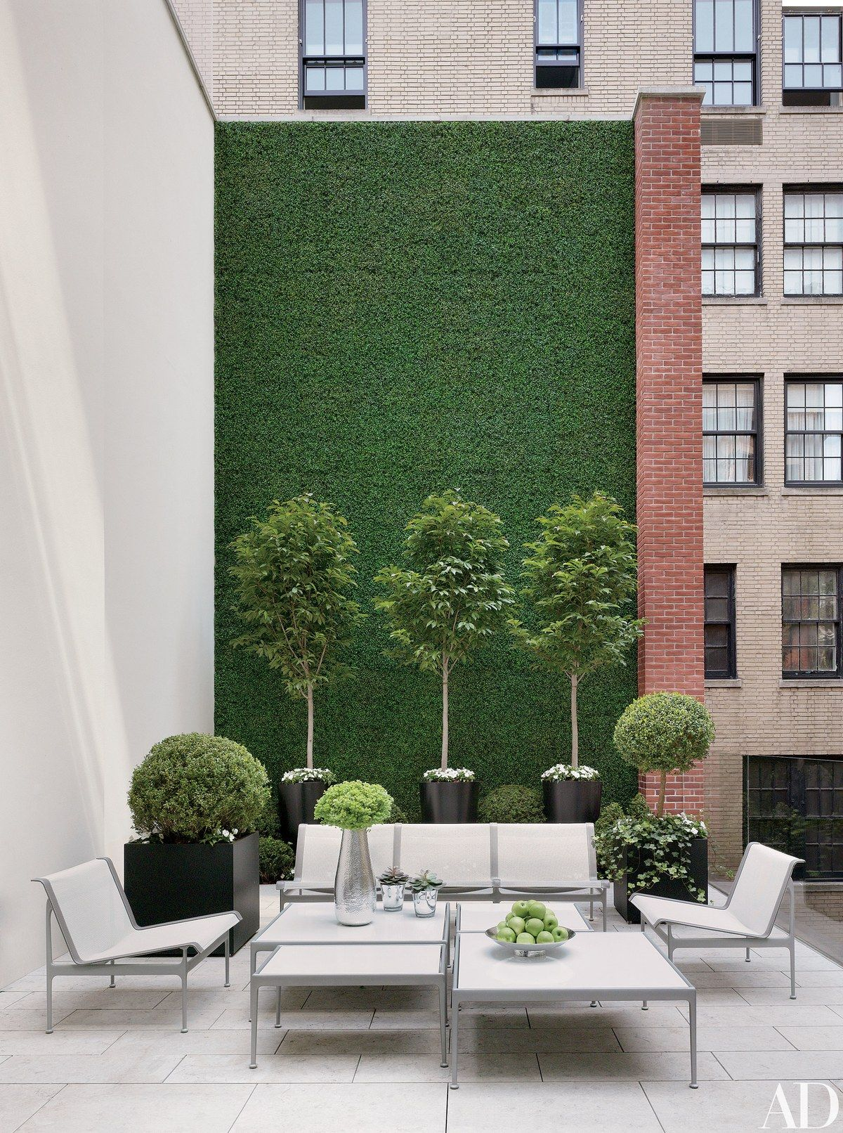 A masonry wall blanketed in faux boxwood offsets outdoor furniture by Richard Schultz and limestone paving.