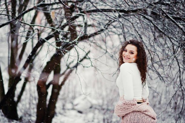 curly brunette girl background falling snow fashion portrait at snowy