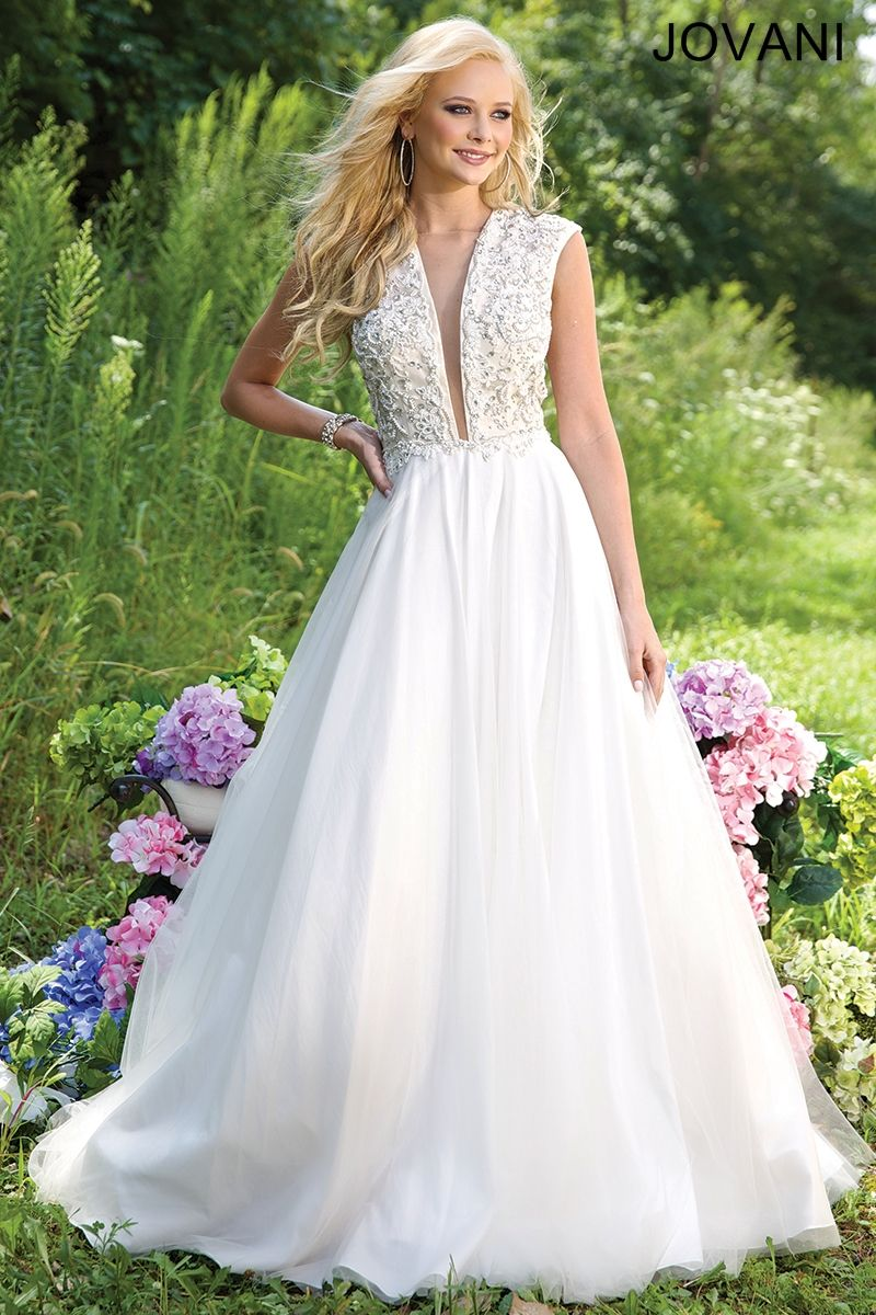 Breathtaking cap sleeve ballgown features a plunging neckline with a