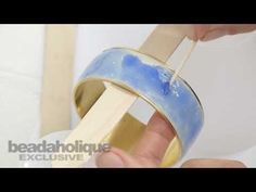 How to Add 2-Part Resin to a Curved Surface In this video tutorial for Beadaholique, guest designer Becky Nunn of Nunn Design shows how to apply 2-part resin to a curved surface. In the video she makes a bangle bracelet and is able to apply resin around the entire circumference. This innovative technique can easily be adapted to other curved surfaces.