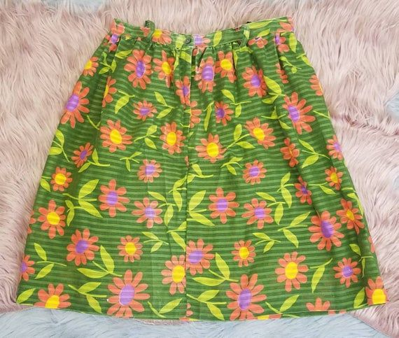 70s flowers #70s Vintage late 60s early 70s flower power skirt. Semi sheer striped green poly cotton fabric with a bright floral pattern. Pink flowers with chartreuse stems and purple and yellow centers. Main green color is a little lighter and brighter than it shows in the pics. Lined with a black semi sheer poly cotton under skirt. Buttons at the waist in the back and zips part way with a metal zipper. Belt loops around the waist. Hem sits just above the knee. Total flower power vibes! Good vi