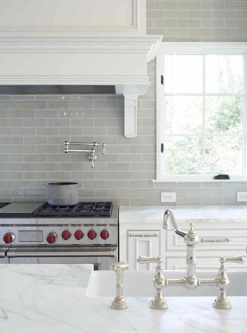 Gray glass kitchen backsplash with carrera marble counters in a pretty traditional white kitchen nickel faucet and wolf range