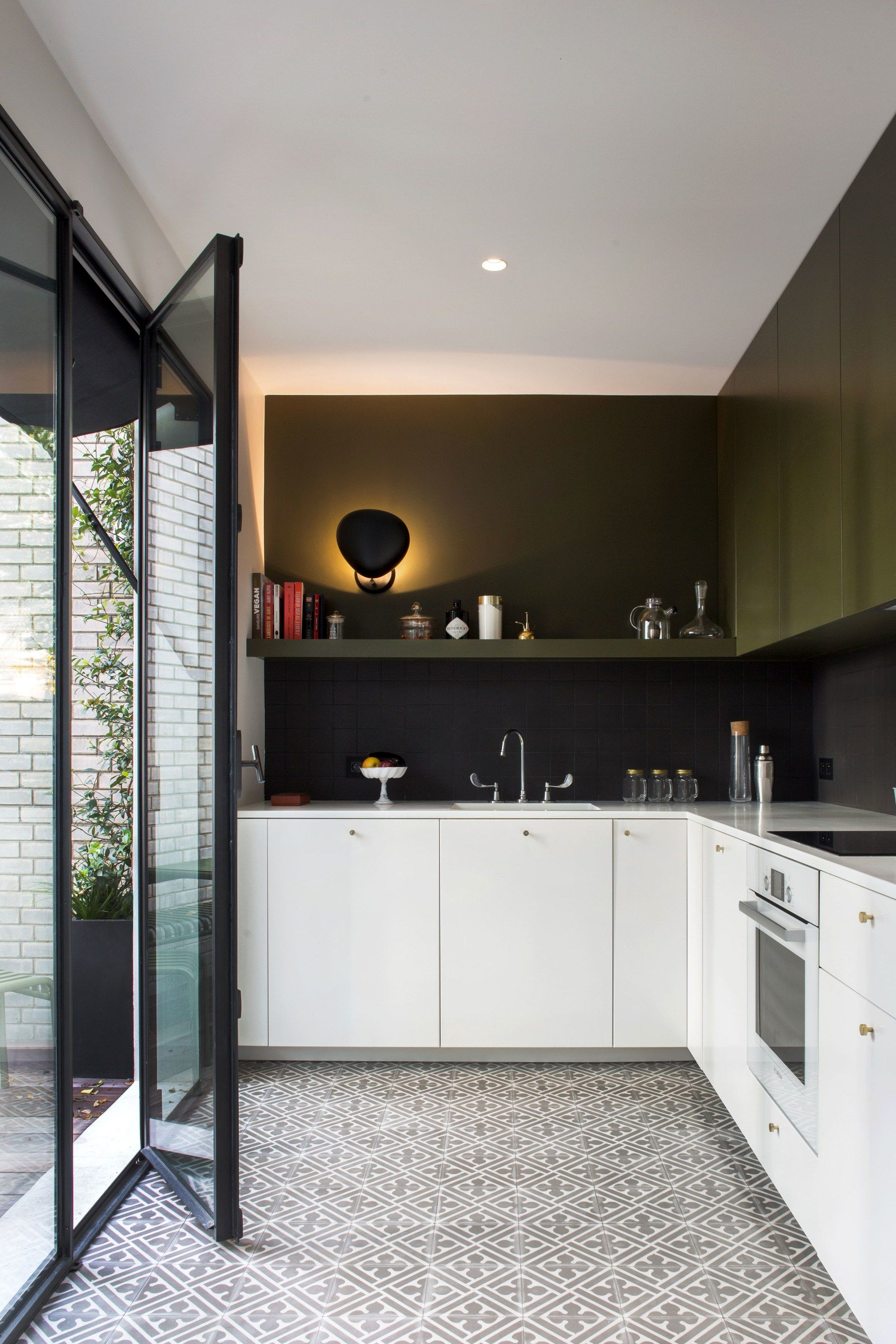 In This 2 Story Paris Apartment There S A Surprise At Every Turn Small White Kitchens Green Kitchen Cabinets Green Kitchen
