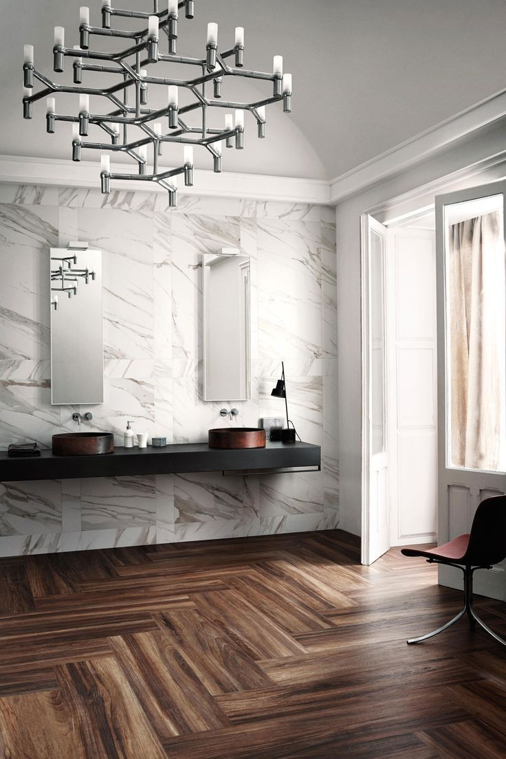 Calacatta marble walls wide plank herringbone wood floors and crisp chandelier