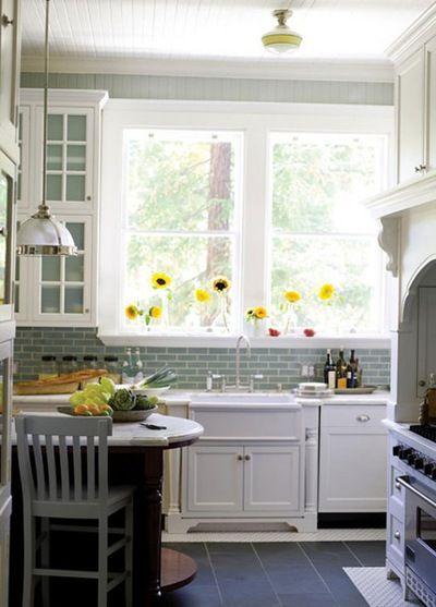 white cabinets, white countertop, gray flooring and blue backsplash