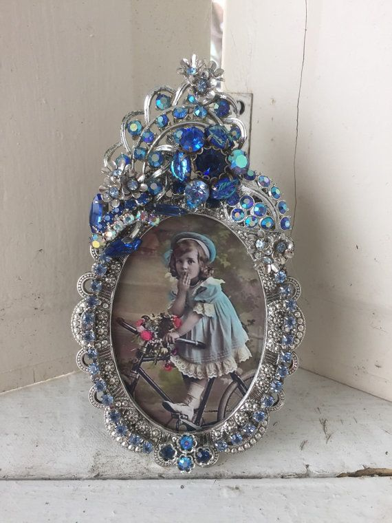 This is a beautiful picture frame that is done in vintage rhinestones and old jewelry parts. Pretty sparkling clear and aqua rhinestones~   This