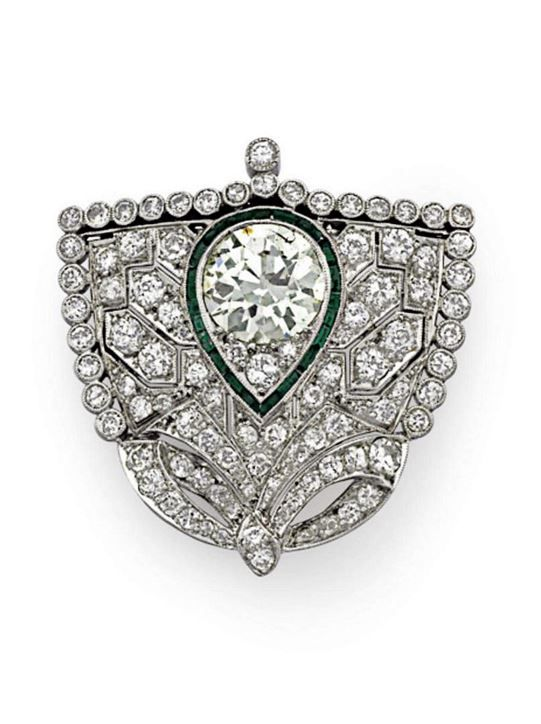 AN ART DECO DIAMOND AND EMERALD BROOCH. Designed as an old-cut diamond shield-shaped plaque trimmed with a collet-set old-cut diamond border, centering upon a cluster of old-cut diamonds with calibré-cut emerald pear-shaped surround, with pendant hook for suspension, circa 1925.