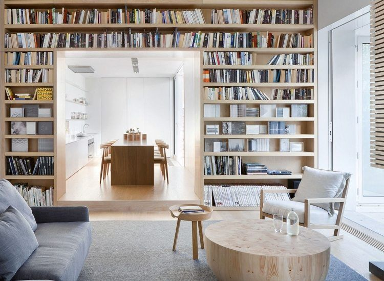 große Regalwand für Bücher und Blick vom Wohnzimmer zur Küche