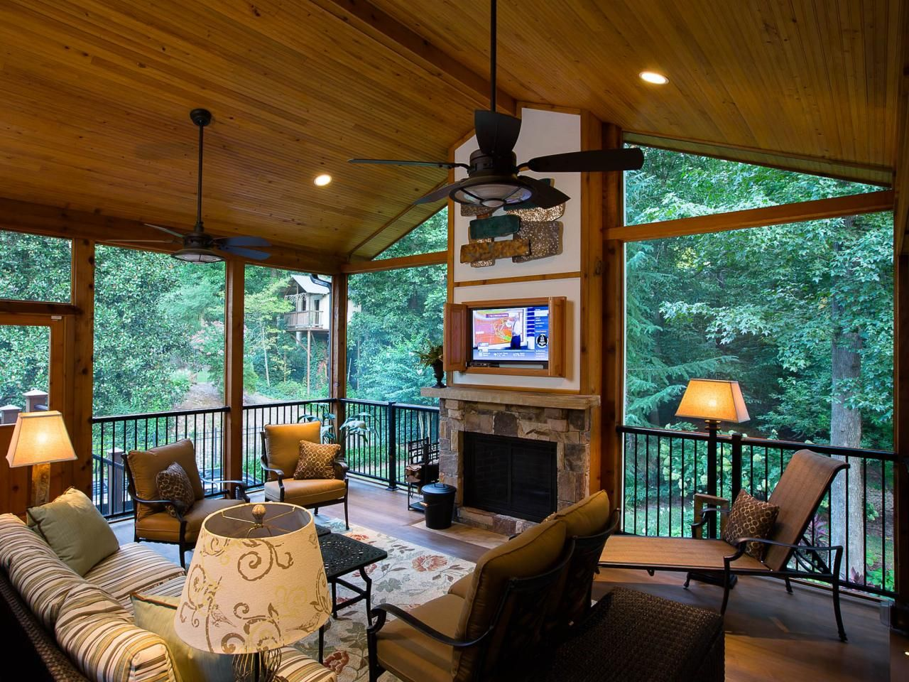 A rustic covered porch with a fireplace and tv screen Deck fireplace designs