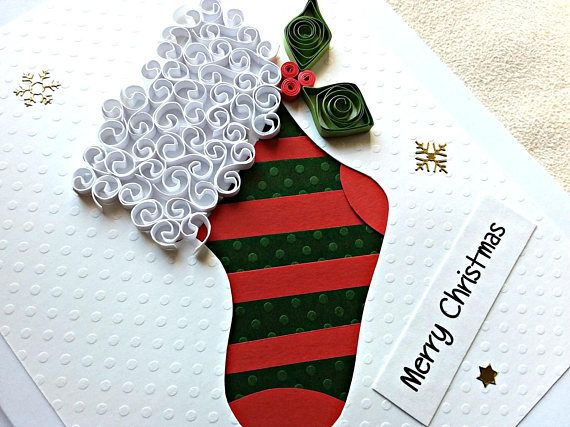 """Each of my handmade cards shapes itself as I manipulate the beautiful papers and ribbons that I work with, making every card unique to that moment. This one is crafted in the shape of a Christmas stocking. The colors are white, ecru, green and red; the accents are gold. The card itself is white. The inside is blank, waiting for your personal Christmas message for a special someone. This card measures 5"""" x 6 ½"""" (12.5 x 16.5 cm). It will arrive with its own coordinated envelope, tucked snugly…"""
