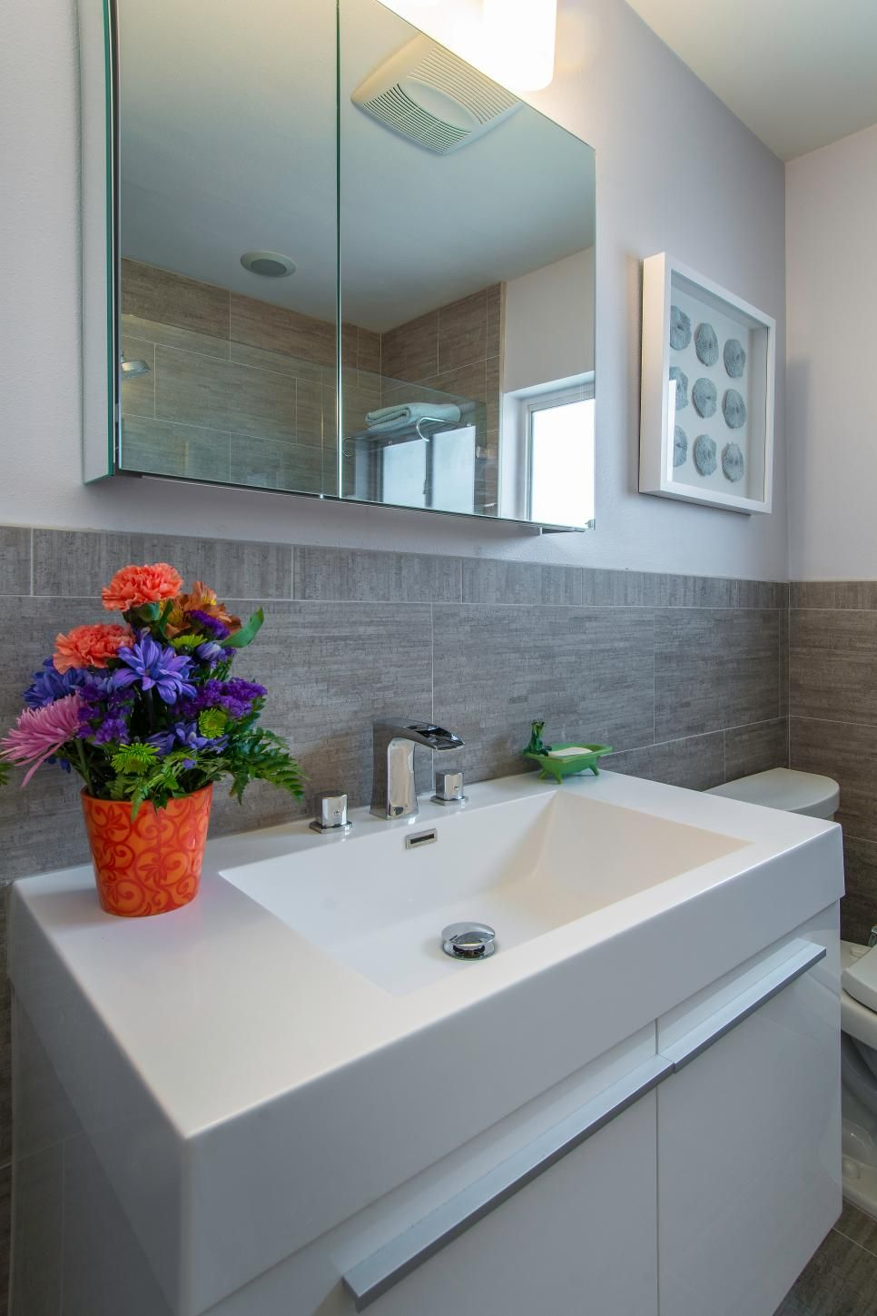 Gray tile work along the floor and running up the wall imparts a ...