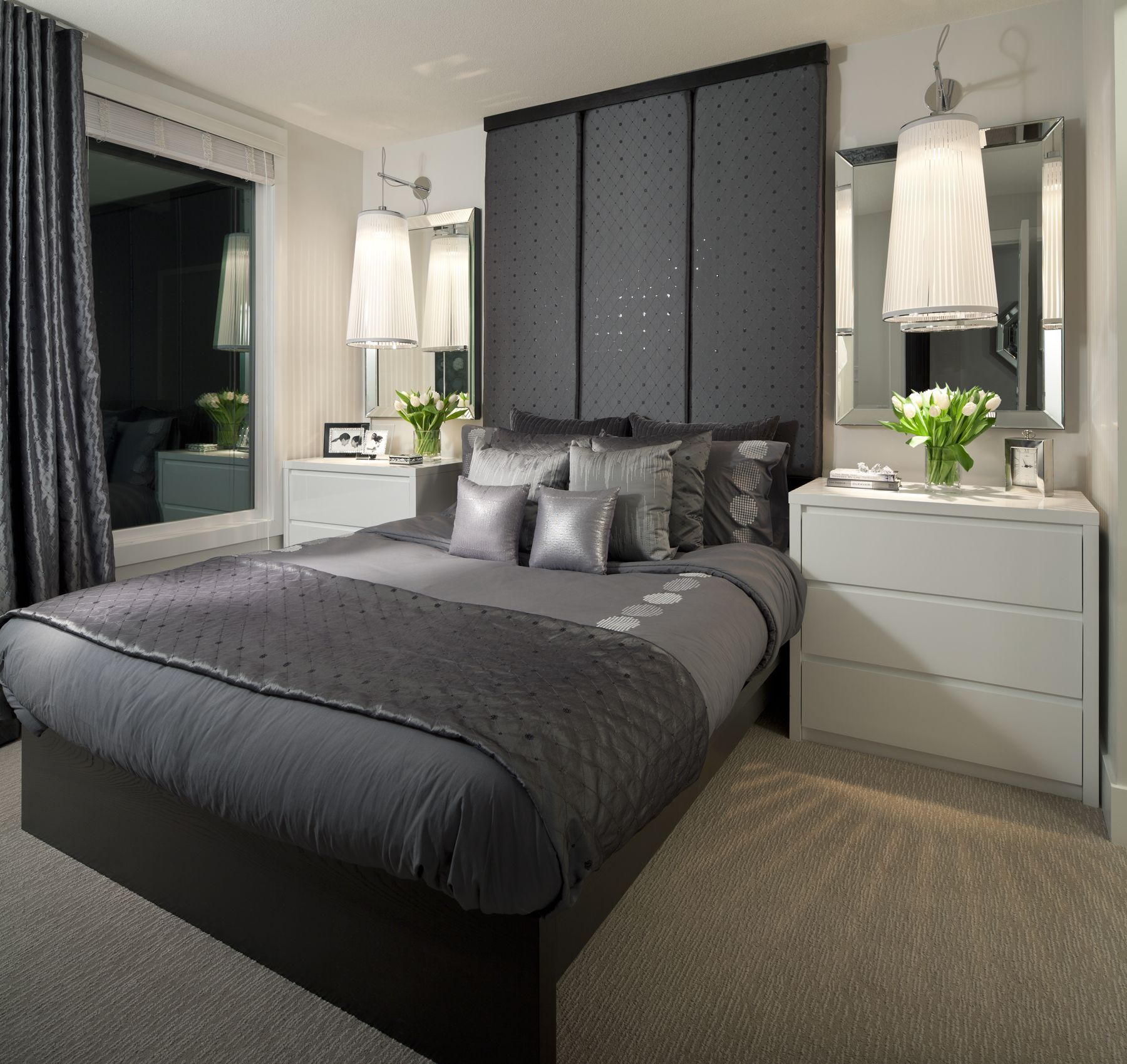 A Contemporary Bedroom With An Upholstered Headboard, Large Wall Sconces