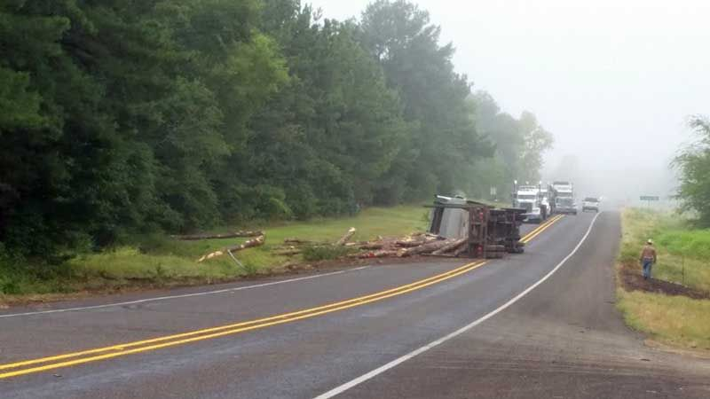 log truck lays on its side after a wreck  Gilmer Texas | Big